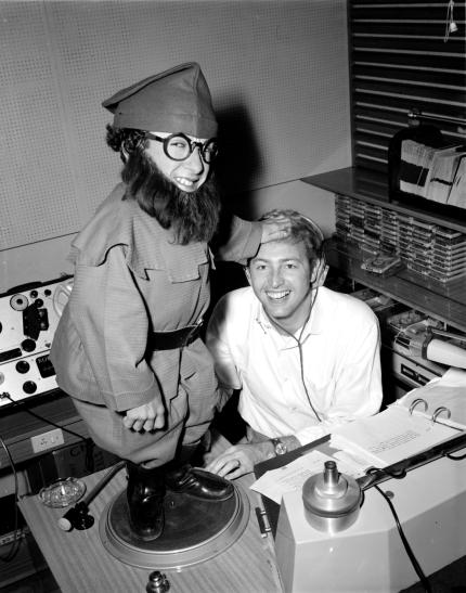 Jimmy Hannan and a Christmas elf performer in the 3UZ studios, 20 December 1968. [UZ 3571] Laurie Richards Collection. Performing Arts Collection, Arts Centre Melbourne.